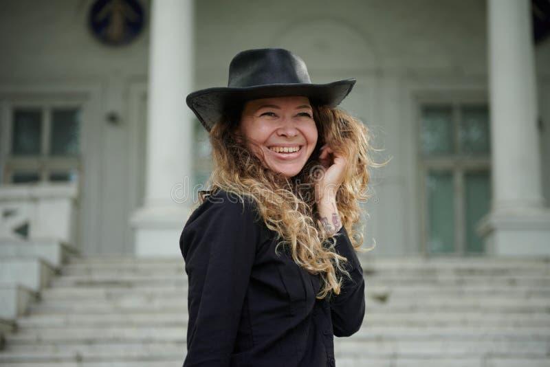 在黑衬衣、帽子和宽长裤打扮的时兴的女孩摆在老白色房子附近 免版税图库摄影