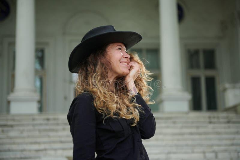 在黑衬衣、帽子和宽长裤打扮的时兴的女孩摆在老白色房子附近 库存图片