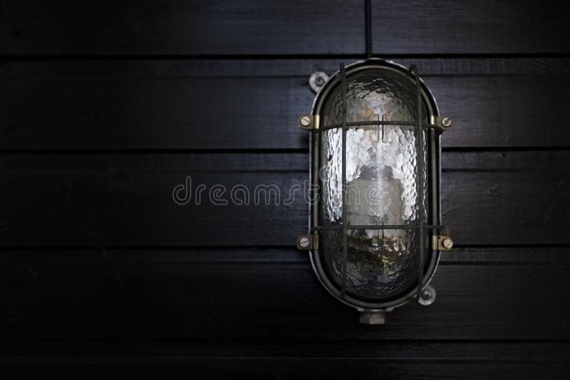在黑被排行的墙壁的葡萄酒壁灯 免版税库存图片