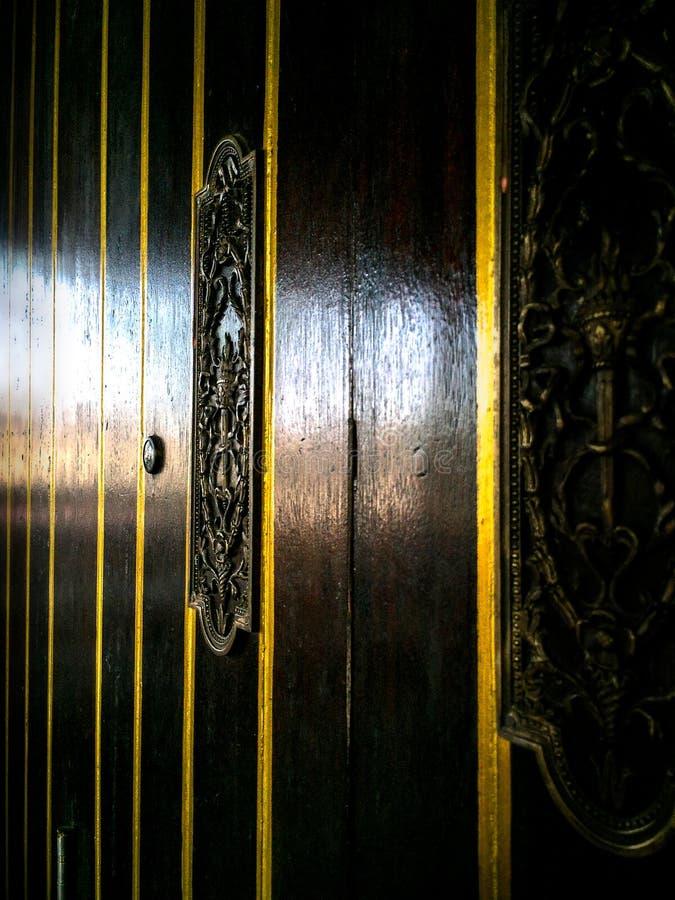 在黑褐色木门的华丽黄铜装饰 免版税库存图片