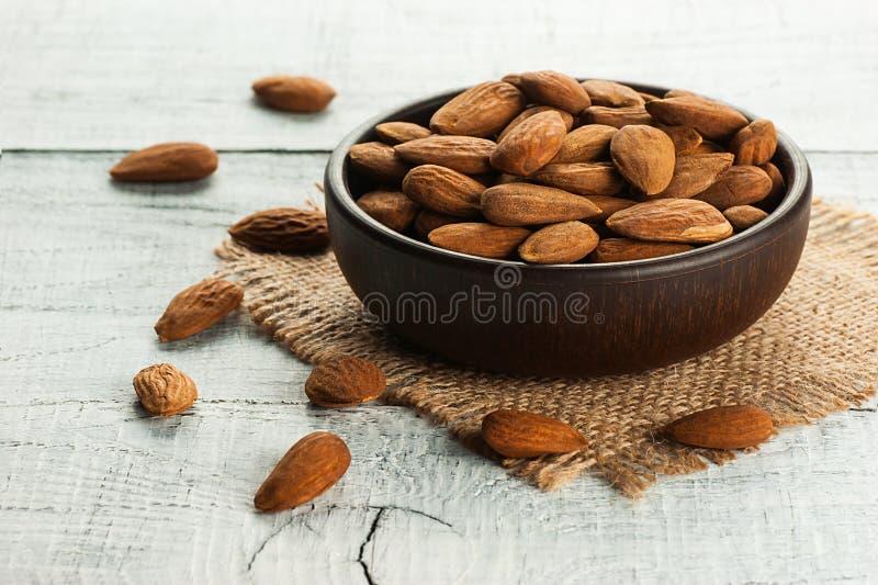 在黑褐色碗的杏仁坚果在土气葡萄酒木桌和粗麻布大袋上 杏仁与拷贝空间的背景概念 库存照片