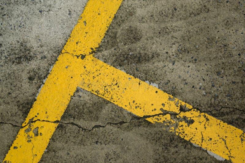 在黑路面的黄色停车位线 库存照片