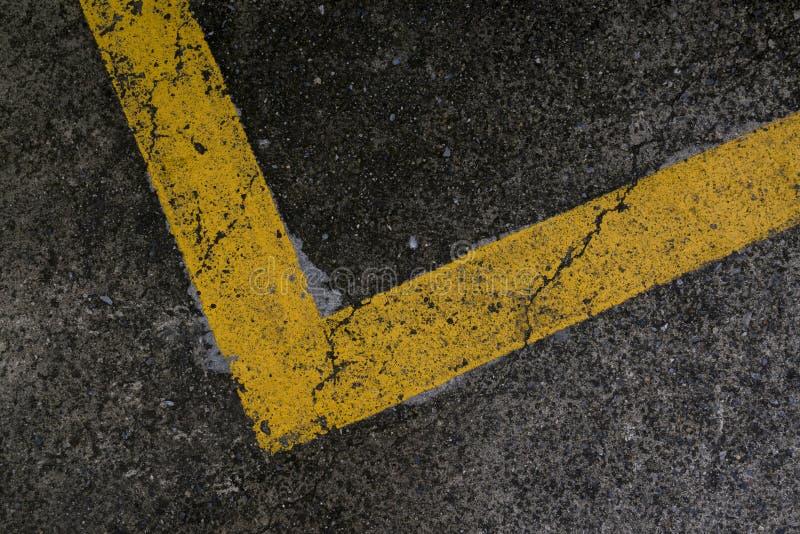 在黑路面的黄色停车位线 免版税库存图片
