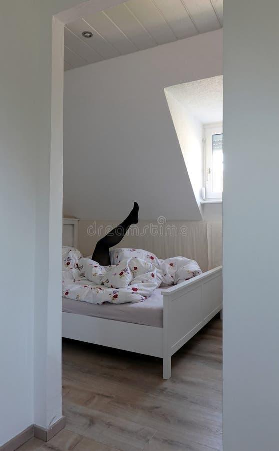在黑长袜的性感的女性腿从毯子下面上升  免版税库存照片
