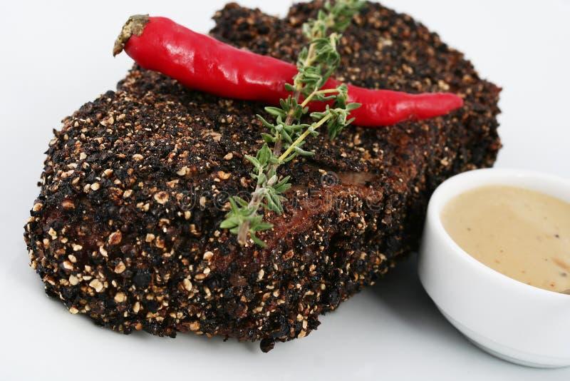 在黑香料和面包渣的牛排 辣子和迷迭香小树枝  库存图片