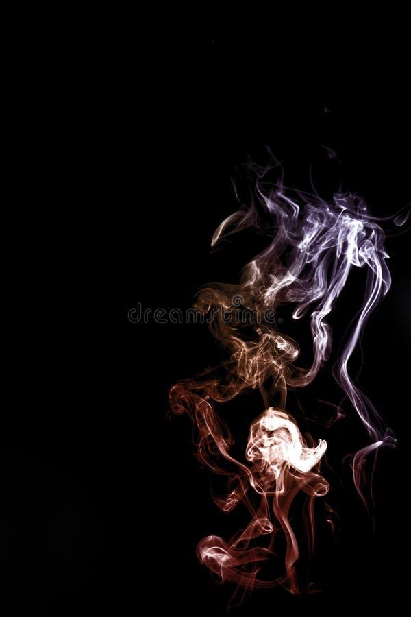 在黑黑暗的背景的五颜六色的烟 免版税图库摄影