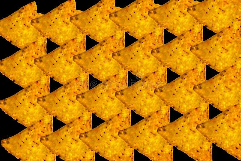 在黑backround的摘要黄色三角烤干酪辣味玉米片 免版税库存图片
