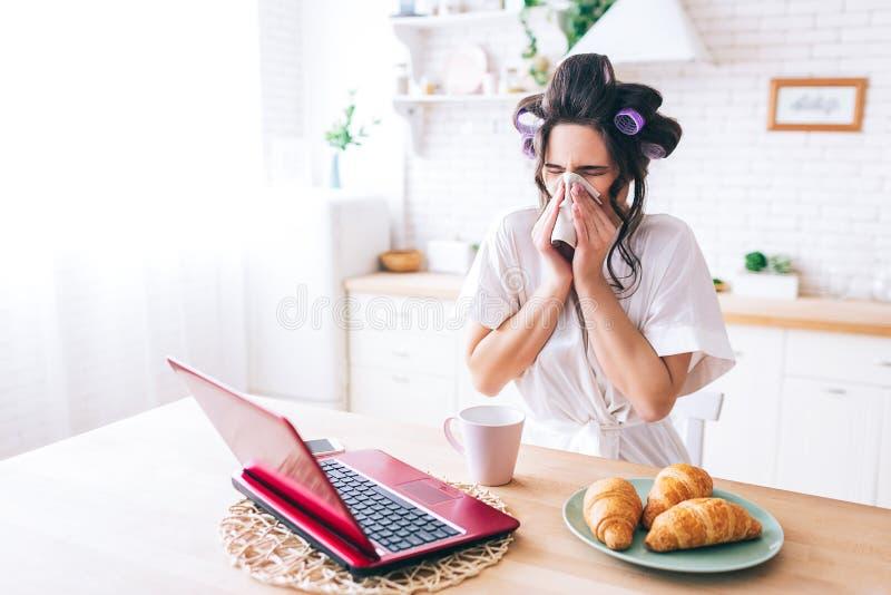 在鼻子附近的年轻病的妇女举行组织 看在膝上型计算机 不适的管家电影 流行性感冒 单独家 免版税库存图片