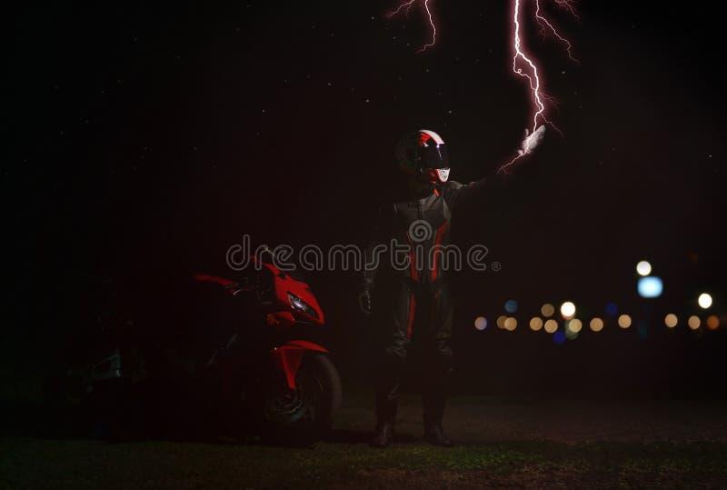 在齿轮和盔甲的车手接触一道闪电 库存图片