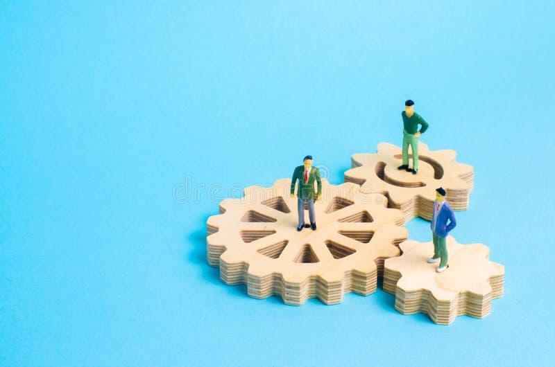 在齿轮的人立场 企业想法和投资的概念,合作和配合与商务伙伴和雇员 图库摄影