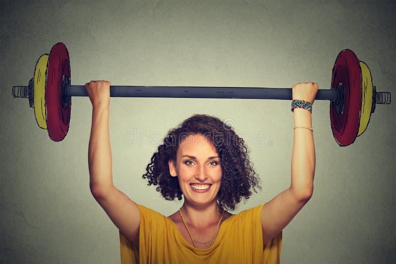 在头上的强的年轻人举的杠铃用两只手 免版税图库摄影