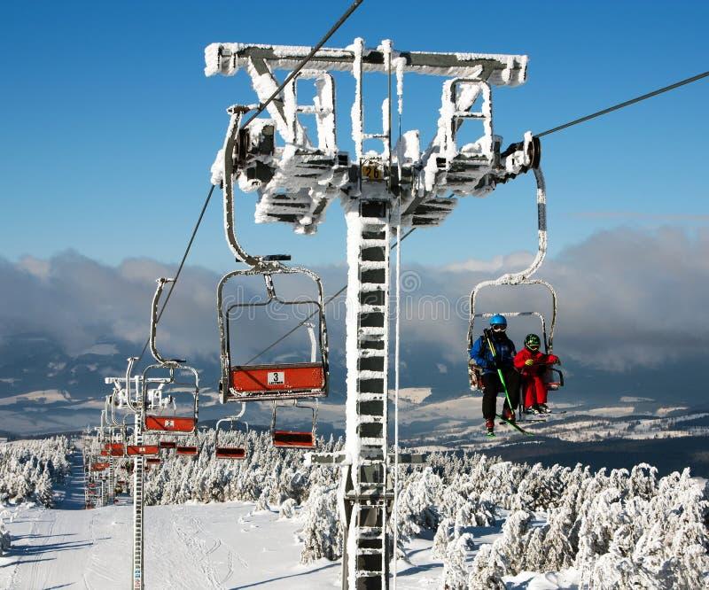 在登上Serak的升降椅下坡滑雪者的 库存图片