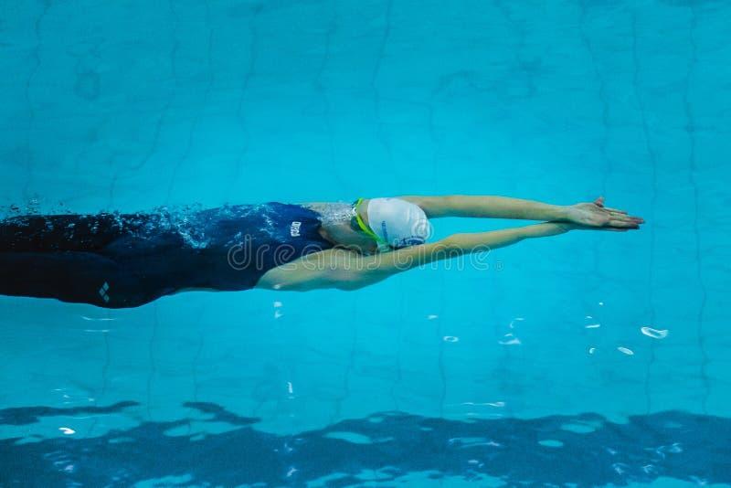 在水下的女孩游泳在仰泳以后开始  免版税库存照片