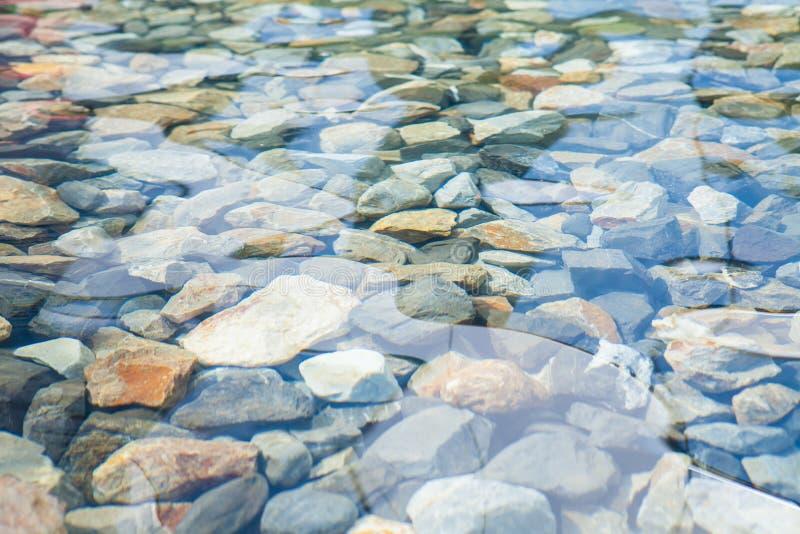 在水下的小卵石与太阳在水中反射了 库存照片