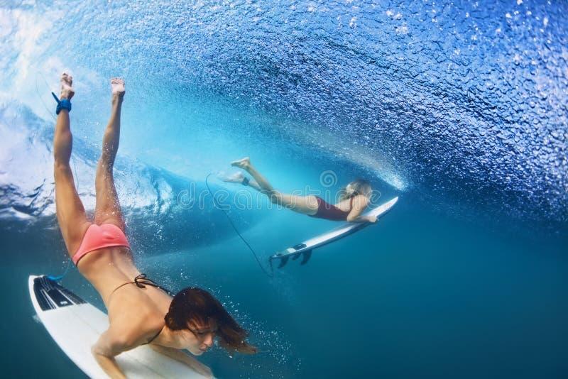 在水下的美好的冲浪者女孩潜水与水橇板 免版税库存图片