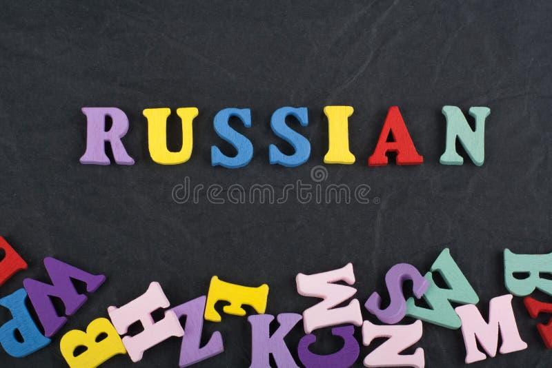 在从五颜六色的abc字母表块木信件组成的黑委员会背景,广告文本的拷贝空间的俄罗斯词 免版税库存图片