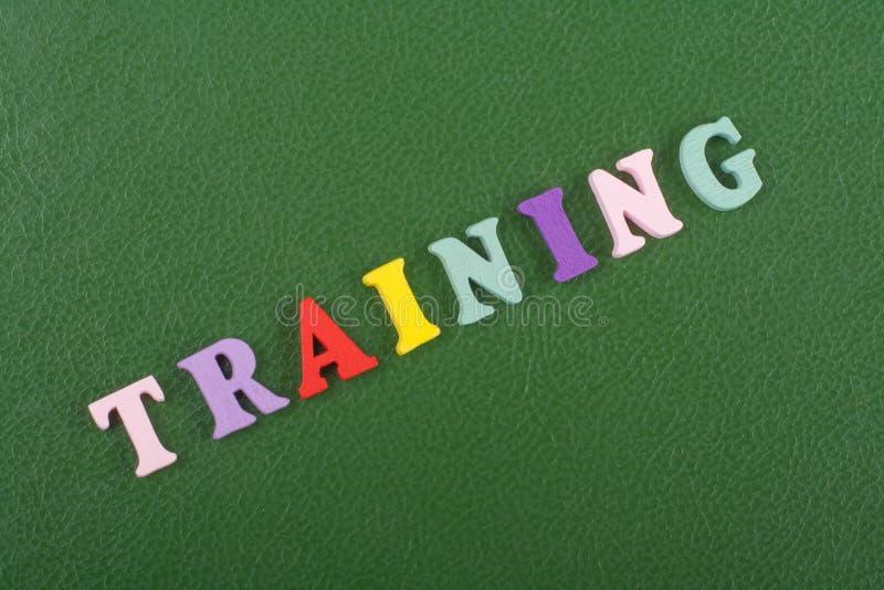 在从五颜六色的abc字母表块木信件组成的绿色背景,广告文本的拷贝空间的训练词 免版税库存照片