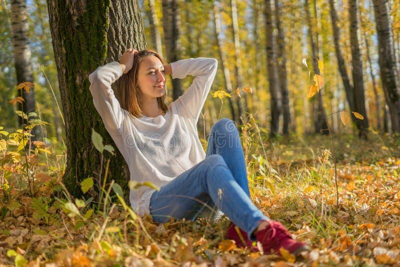 在年轻人之下的女孩坐的结构树 库存图片