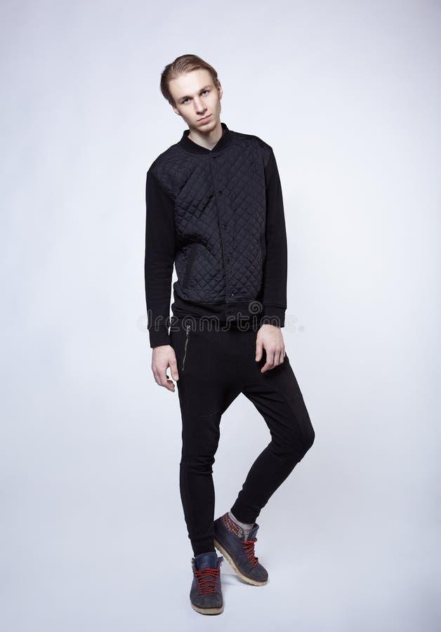 在黑人衣服的年轻白肤金发的男性模型 库存图片