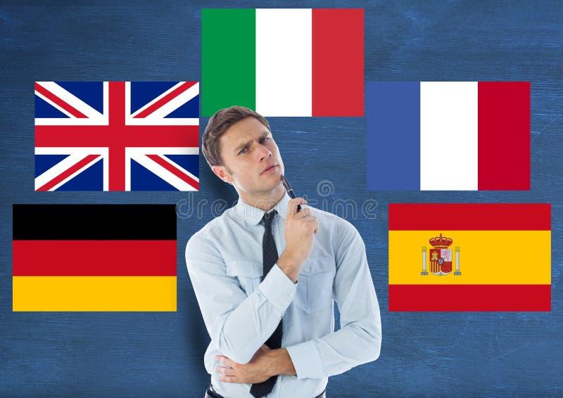 在年轻人附近的主要语言旗子 背景蓝色黑暗的无限 库存照片