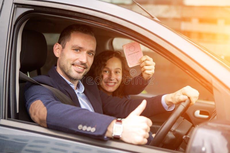 在他们全新的汽车的年轻商人夫妇 库存照片