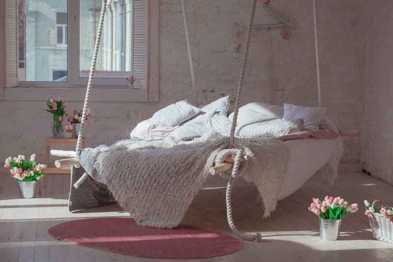 在经典斯堪的纳维亚样式的白色顶楼内部 从天花板暂停的垂悬的床 舒适大被折叠的米黄格子花呢披肩 图库摄影