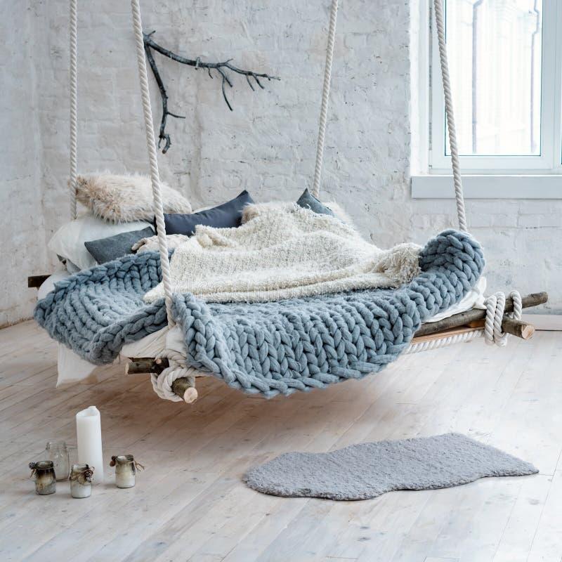 在经典斯堪的纳维亚样式的白色顶楼内部 从天花板暂停的垂悬的床 舒适大被折叠的灰色格子花呢披肩 库存照片