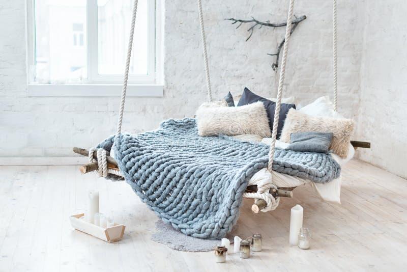在经典斯堪的纳维亚样式的白色顶楼内部 从天花板暂停的垂悬的床 舒适大被折叠的灰色格子花呢披肩 免版税图库摄影