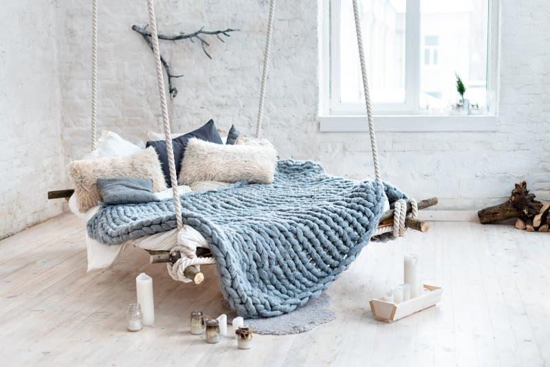 在经典斯堪的纳维亚样式的白色顶楼内部 从天花板暂停的垂悬的床 舒适大被折叠的灰色格子花呢披肩 免版税库存照片