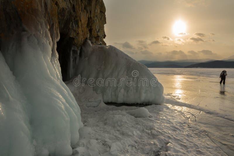 在洞穴前的弗罗斯特岩石的 日落冬天风景在贝加尔湖 免版税库存图片
