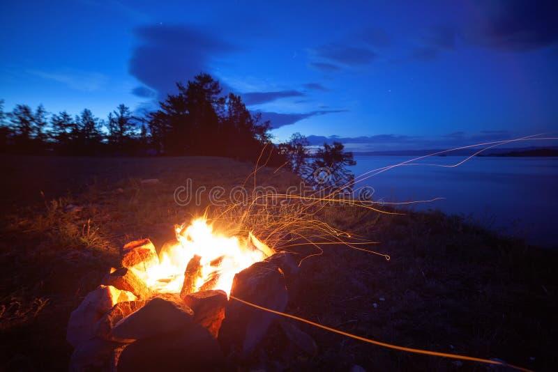 在贝加尔湖岸的篝火夜  免版税库存照片