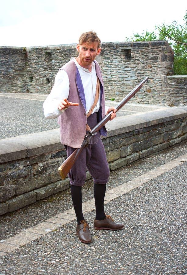 在1688年历史的围困Derry和有步枪的这个学徒男孩的再制定要求在城市墙壁上的支持 免版税库存照片