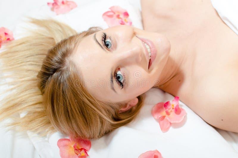 在年轻可爱的美丽的白肤金发的妇女蓝眼睛女孩愉快微笑的特写镜头在与花瓣的温泉做法期间在她附近 库存照片