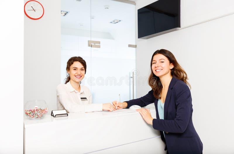 在总台管理员后的友好的妇女有顾客的 库存照片