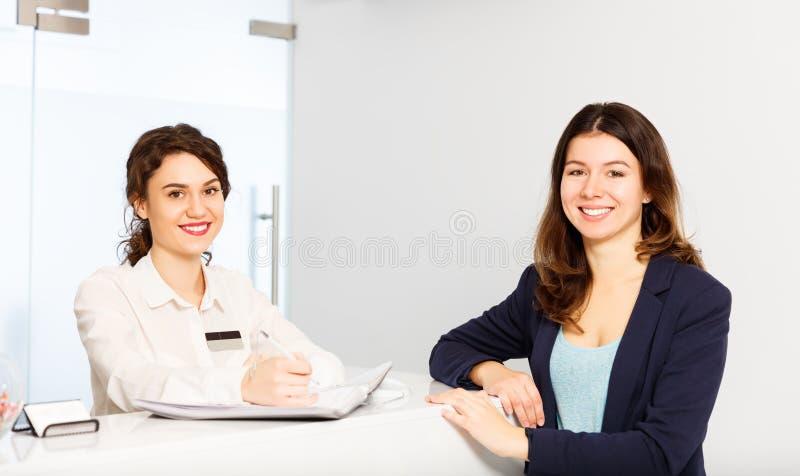在总台管理员后的友好的妇女有顾客的 免版税库存照片