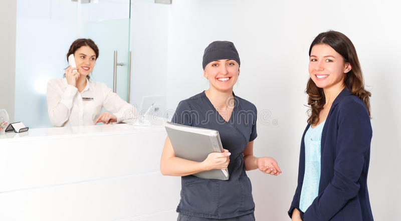 在总台管理员后的友好的妇女有a医生的 图库摄影