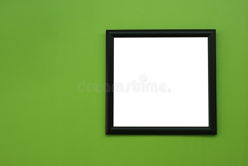 在绿叶颜色油漆墙壁backgroun的黑空白的画框 库存照片