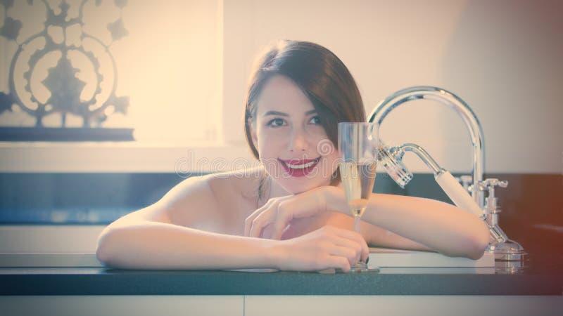 在浴和举行c的玻璃美丽的少妇 免版税图库摄影