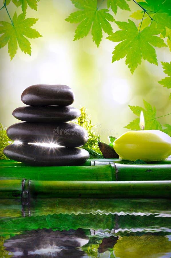被堆积的黑石头和蜡烛在竹子 反映在水本质上 安静和放松的概念 供