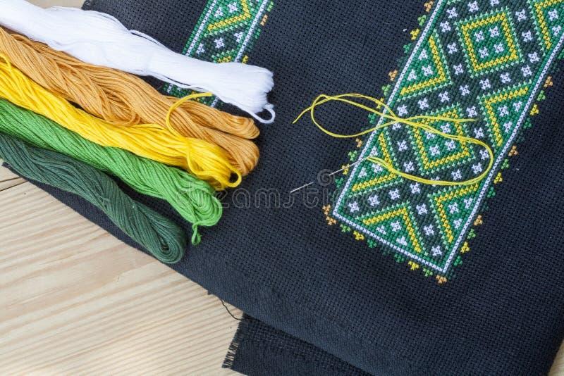 在黑织品和螺纹刺绣的乌克兰刺绣在一张轻的木桌上 免版税库存照片