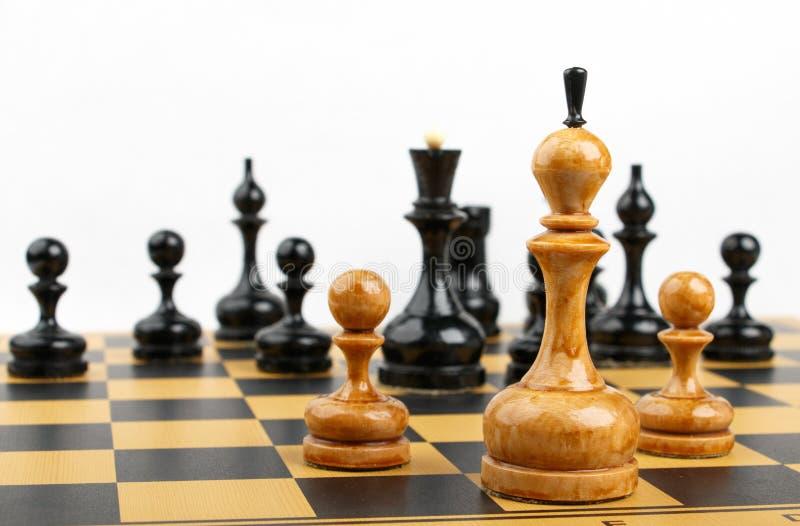 在黑图对面的三个白色棋子 免版税库存图片