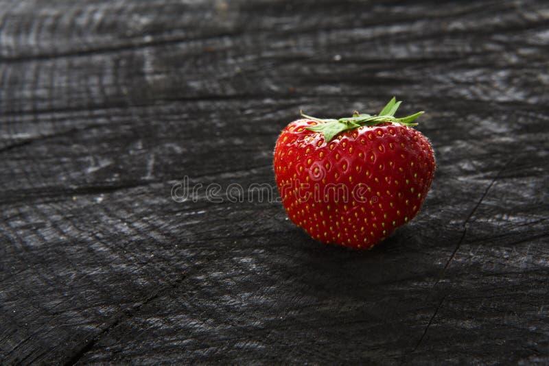 在黑土气木背景的红色新鲜的草莓 图库摄影