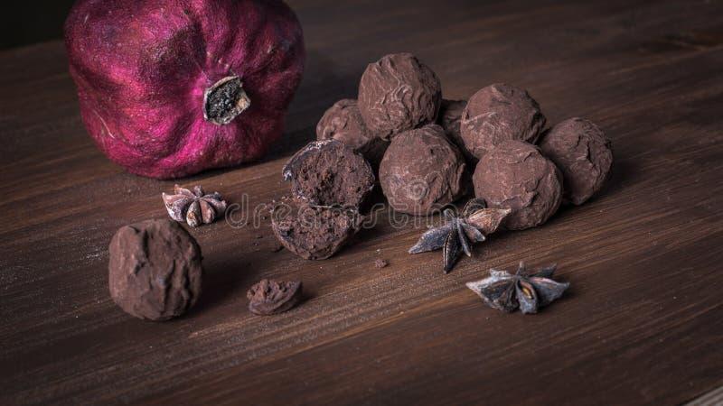 在织地不很细木背景的块菌状巧克力 库存照片