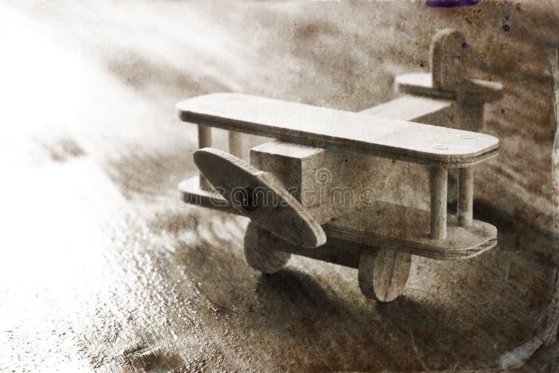 在织地不很细木背景的木飞机玩具 棒图象夫人减速火箭的抽烟的样式 黑白老牌照片 图库摄影