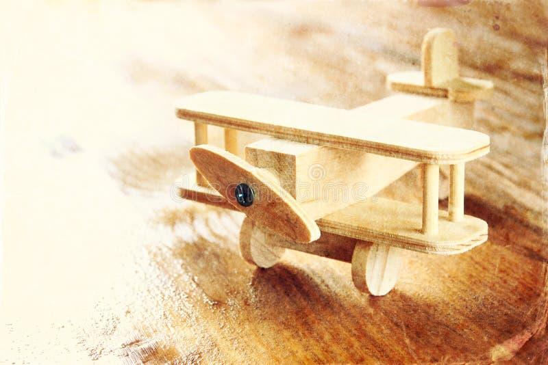 在织地不很细木背景的木飞机玩具 棒图象夫人减速火箭的抽烟的样式 库存图片