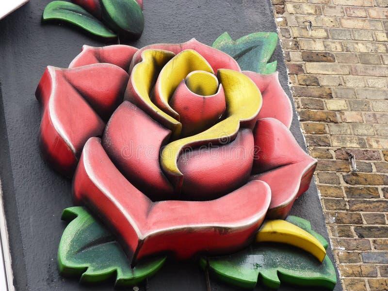 在黑墙壁上的美丽的红色黄色罗斯 免版税库存照片