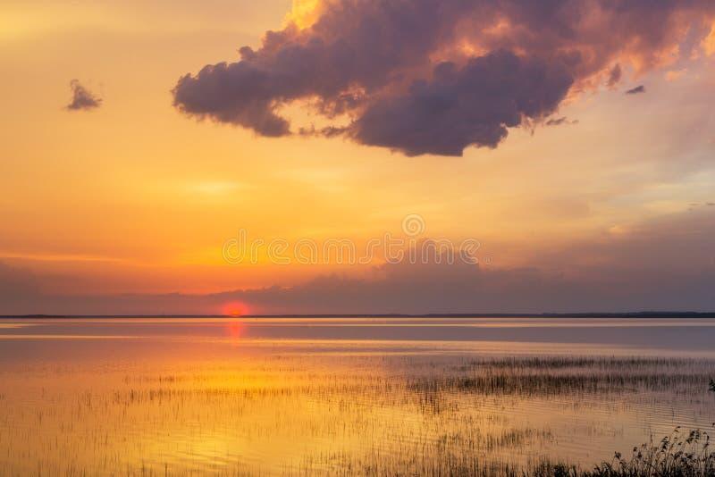 在水夏天晚上云彩湖的日落 库存图片