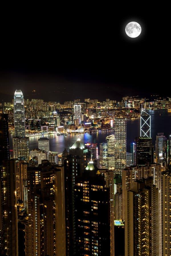 在维多利亚港在晚上,香港的满月 库存图片