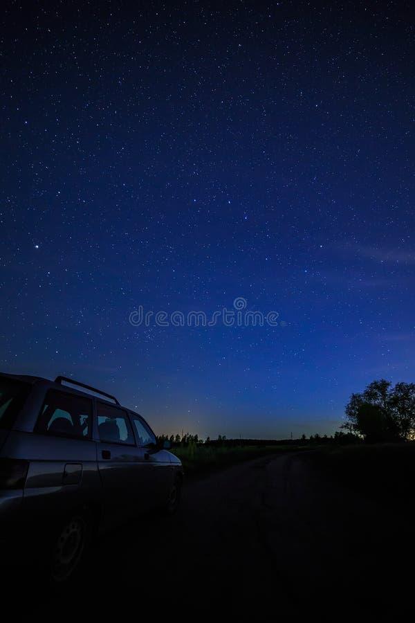 在满天星斗的背景天空和银河的旅游汽车 库存图片