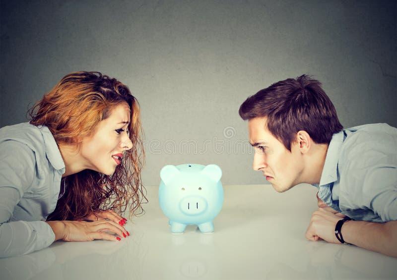 在离婚概念的财务 妻子和丈夫不可能做看存钱罐的解决坐在看彼此的桌上 免版税库存照片